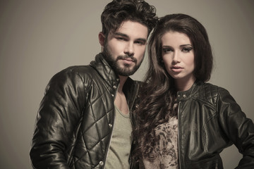 embraced modern couple in leather jackets smiling