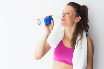 Smiling young woman with towel drinking water