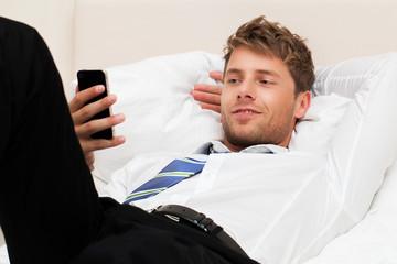 Geschäftsmann im Hotelbett mit Telefon