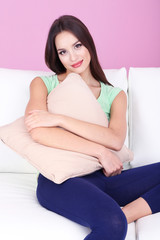 Beautiful young woman relaxing on sofa on pink background