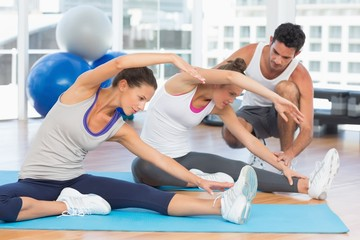 Women doing stretching exercises as trainer helps one