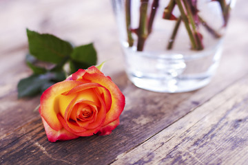 Rose vase next to the wooden table.
