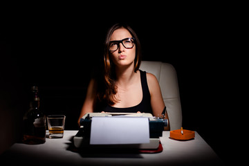 Young female novelist writing a book using typewriter