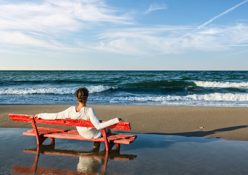 girls sitting on a red bench on the beach
