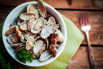 Bowl of Delicious Fresh Steamer Clams with Garlic and Basil on r