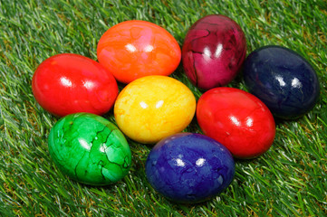 colorful eggs lie on a synthetic grass