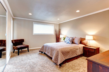 Cozy brown tones bedroom with wood furniture and soft carpet