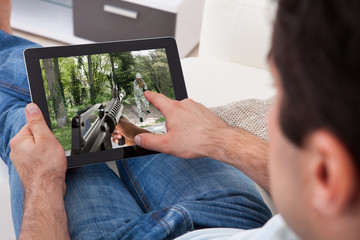Man Playing Game On Tablet Pc