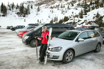 The woman with ski on parking place