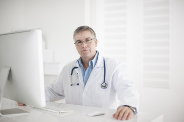 Portrait of handsome mature doctor in office