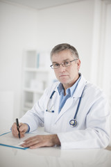mature doctor writing a prescription in his office