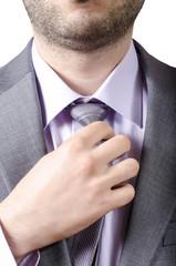 business man adjusting his neck tie