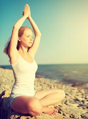 Fototapete - young woman doing yoga on  beach