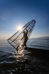 A local fisherman is fishing by boat, Inle lake, Myanmar.