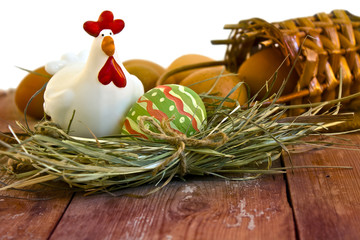 Painted Easter egg and decorative chicken in the nest