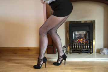 Woman wear black fishnet tights by the fire