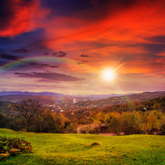 Foto op Plexiglas Rood village on hillside meadow with forest in mountain at sunset