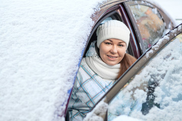 Smiling woman sitting inside of snow covered car