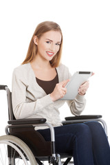 Beautiful casual woman sitting on w wheelchair with tablet.