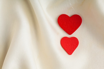 Red wooden decorative hearts on white silk background.