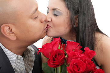 Close up of couple kissing holding a bouquet of red roses