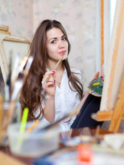 girl paints with oil colors and brushes
