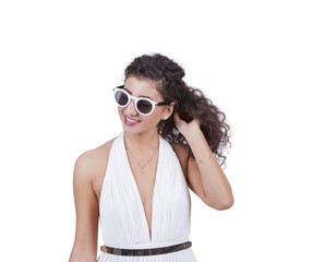 Young female wearing sunglasses and posing against white