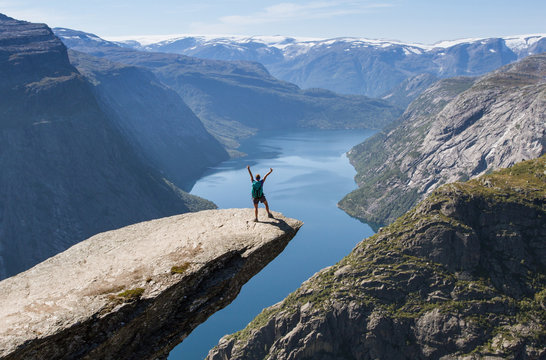 girl with backpack on trolltunga in norway