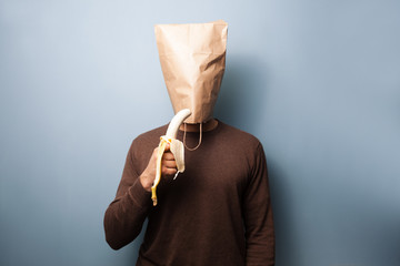 Young man with bag over his head is eating a banana