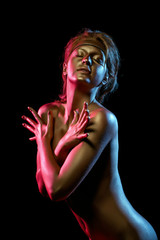 Emotional naked girl posing as golden statue