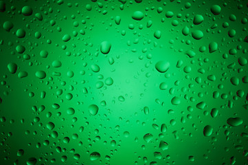 Green water drops on glass surface
