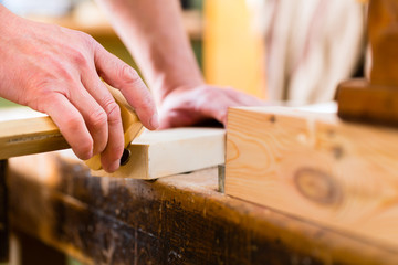 Tischler oder Schreiner mit Werkstück in Tischlerei