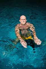 Healthy active senior man with beard in indoor swimming pool. We