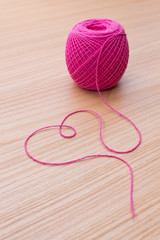 Ball of yarn and heart shape on a wooden table.