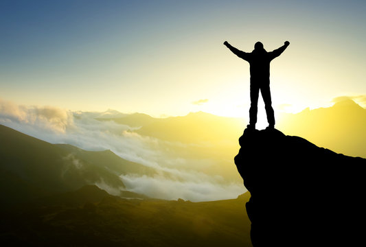 Silhouette of a winner on the mountain top. Active life concept