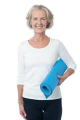 Gym instructor holding blue exercise mat