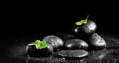Zen stones with mint leaves on a black background
