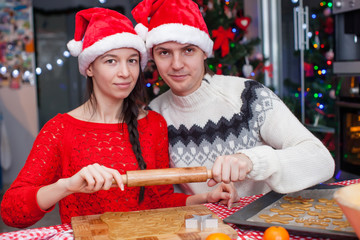 Young happy couple baking Christmas cakes