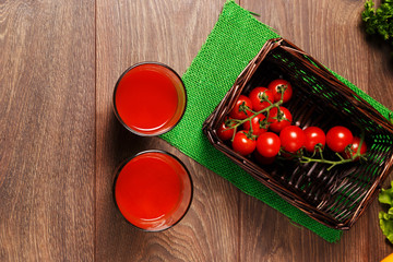 Two glasses of tomato juice and tomatoes in a crate