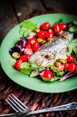 Baked seabass with tomatoes and basil on rustic wooden backgroun