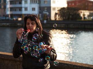 young beautiful woman blows bubbles