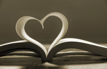 Open book with pages forming heart shape.