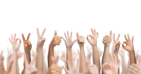 human hands showing thumbs up, ok and peace signs