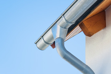 Corner of a house with gutters on a background of blue sky