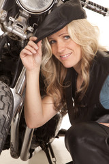 Woman leather hat kneel by motorcycle smile