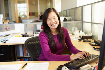 Asian Woman Working At Computer In Modern Office