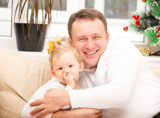 Happy father and child girl hugging and laughing at home