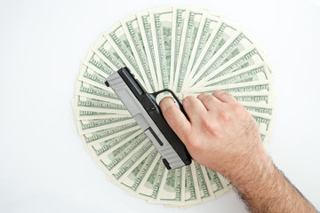 Man holding gun over a stack of money