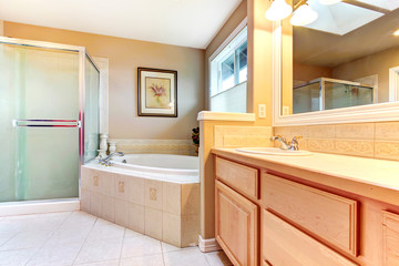 Refreshing bathroom with light wood cabinets, glass shower and b