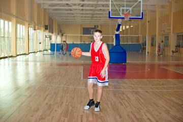 Basketball player with a ball in his hands and a red uniform.